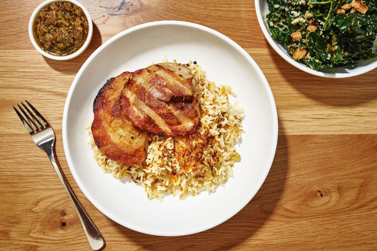 Grilled porchetta sits on a bed of fried rice with a green salad on one side, and a light green chutney on the other