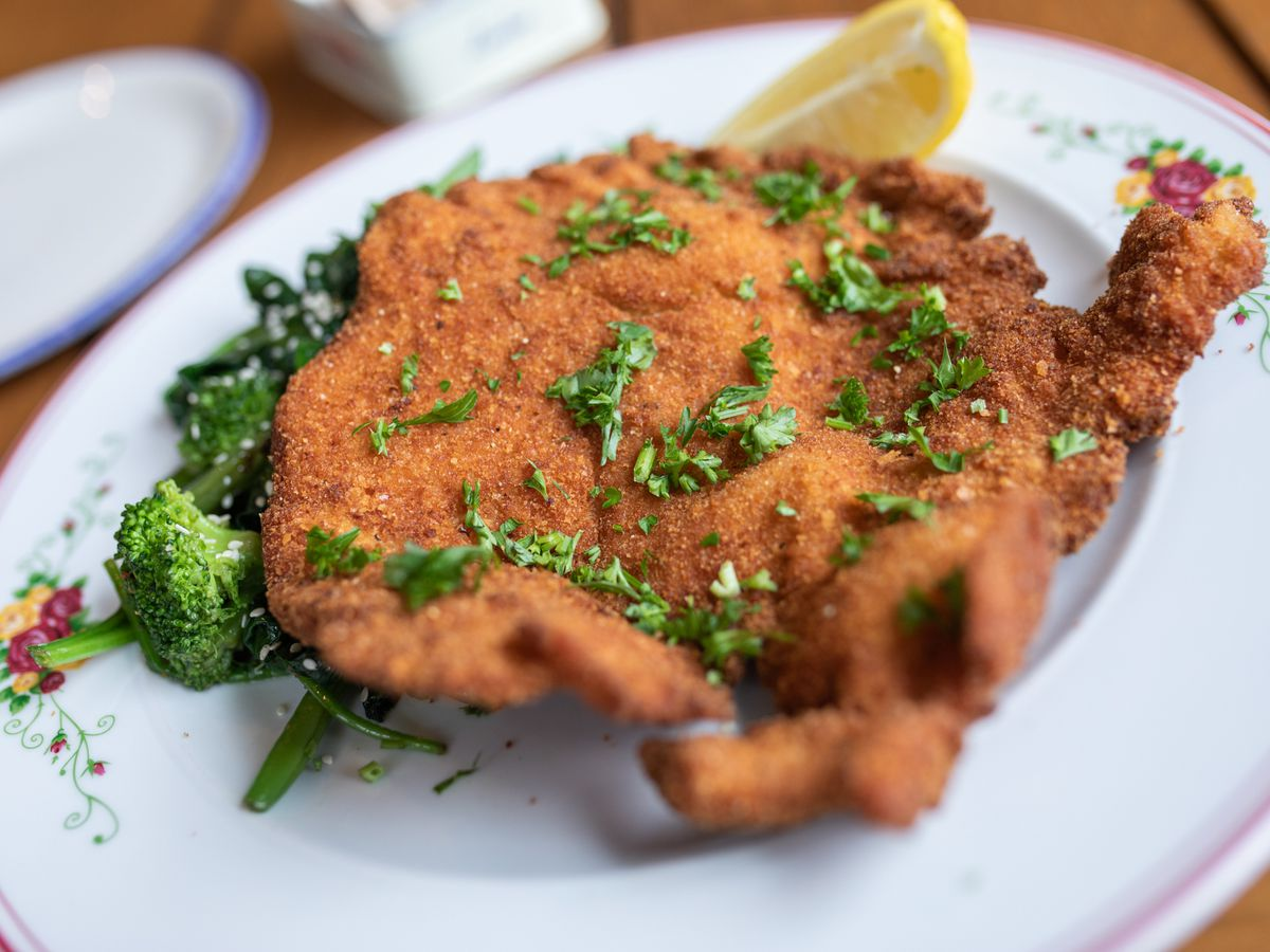 A piece of flattened, breaded, and fried chicken sits on a white plate, topped with chopped green herbs. A slice of lemon and greens are on the side.