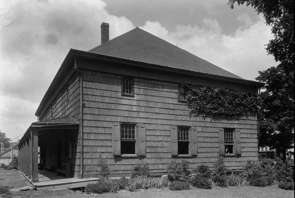 The exterior of a large house with siding. This is a historic image which is in black and white. There is shrubbery on the side of the house.