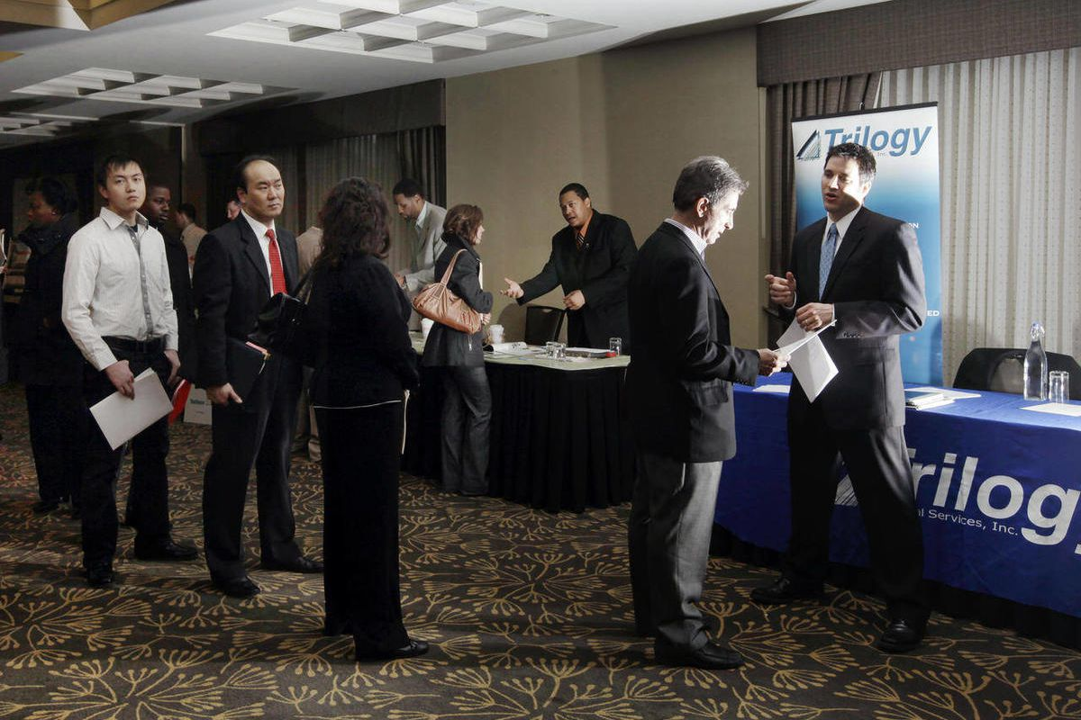 In this Feb. 27, 2012, photo, job seekers line up to speak to Trilogy's Regional Vice President Tom Elkins, far right, at a job fair in Boston.
