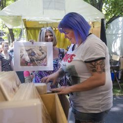 """Katie Krejchi, left, and daughter Katharine Krejchi look through stacks of art by Michael Rohner on the first day of the Utah Arts Festival in Salt Lake City on Thursday, June 22, 2017. """"Every year we come here we have a theme — this year is moths for her and last year it was space,"""" says Katie."""