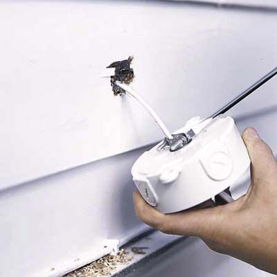 Man Attaches Round Outlet Box To Install Outdoor Garage Floodlights