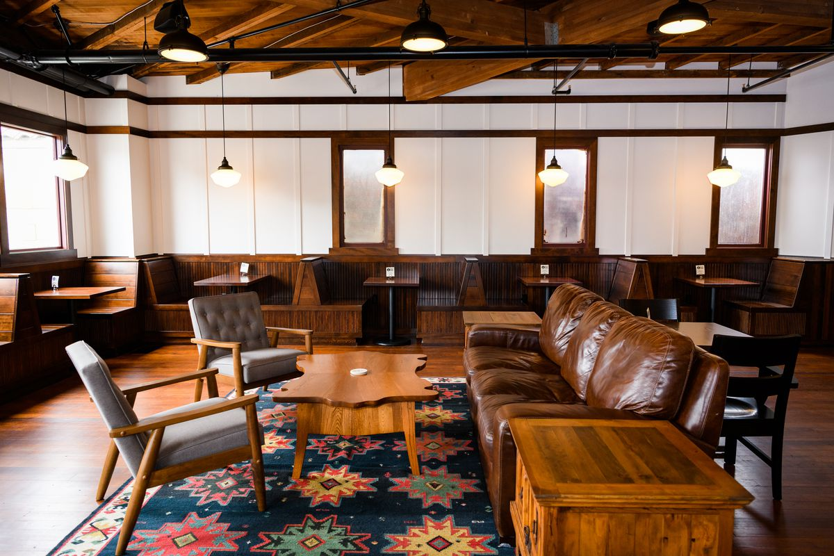 A wooden leather couch sits on a blue patterned rug, along with an irregularly shaped wooden coffee table and two grey cushioned chairs. Small wooden booths line the room.