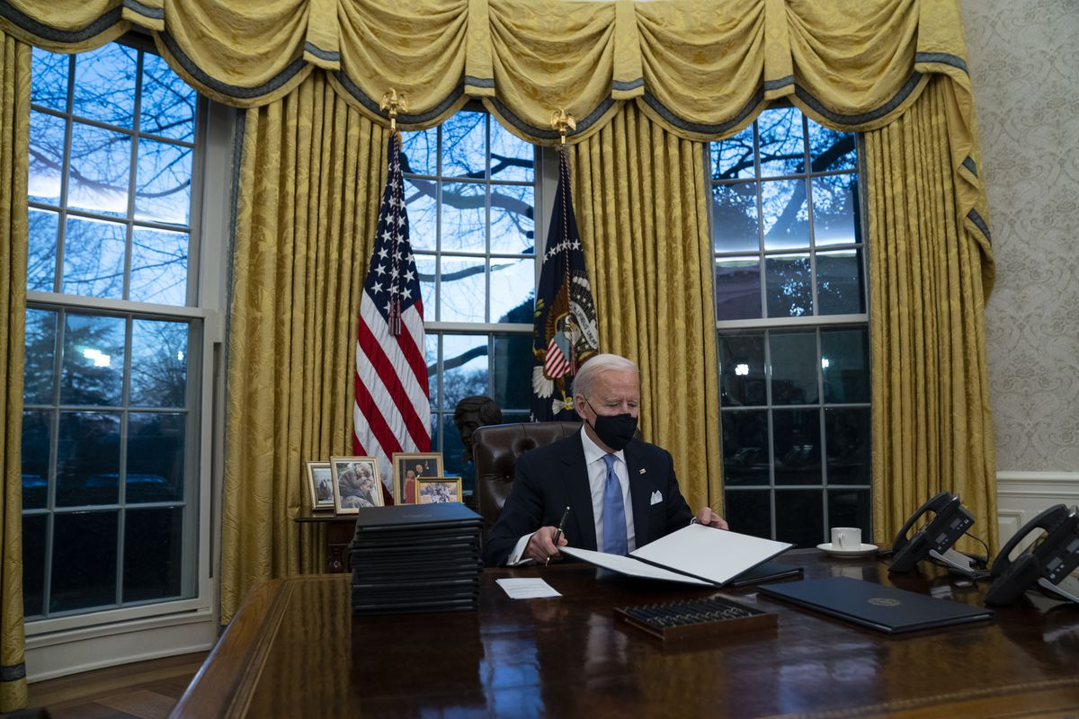 President Joe Biden signs a series of executive orders in the Oval Office of the White House in Washington on Jan. 20, 2021.