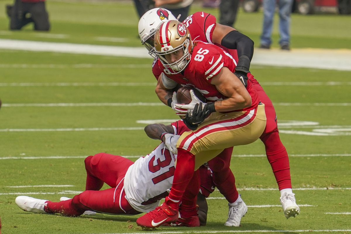 San Francisco 49ers tight end George Kittle is tackled by Arizona Cardinals safety Chris Banjo and middle linebacker Jordan Hicks during the first quarter at Levi's Stadium.