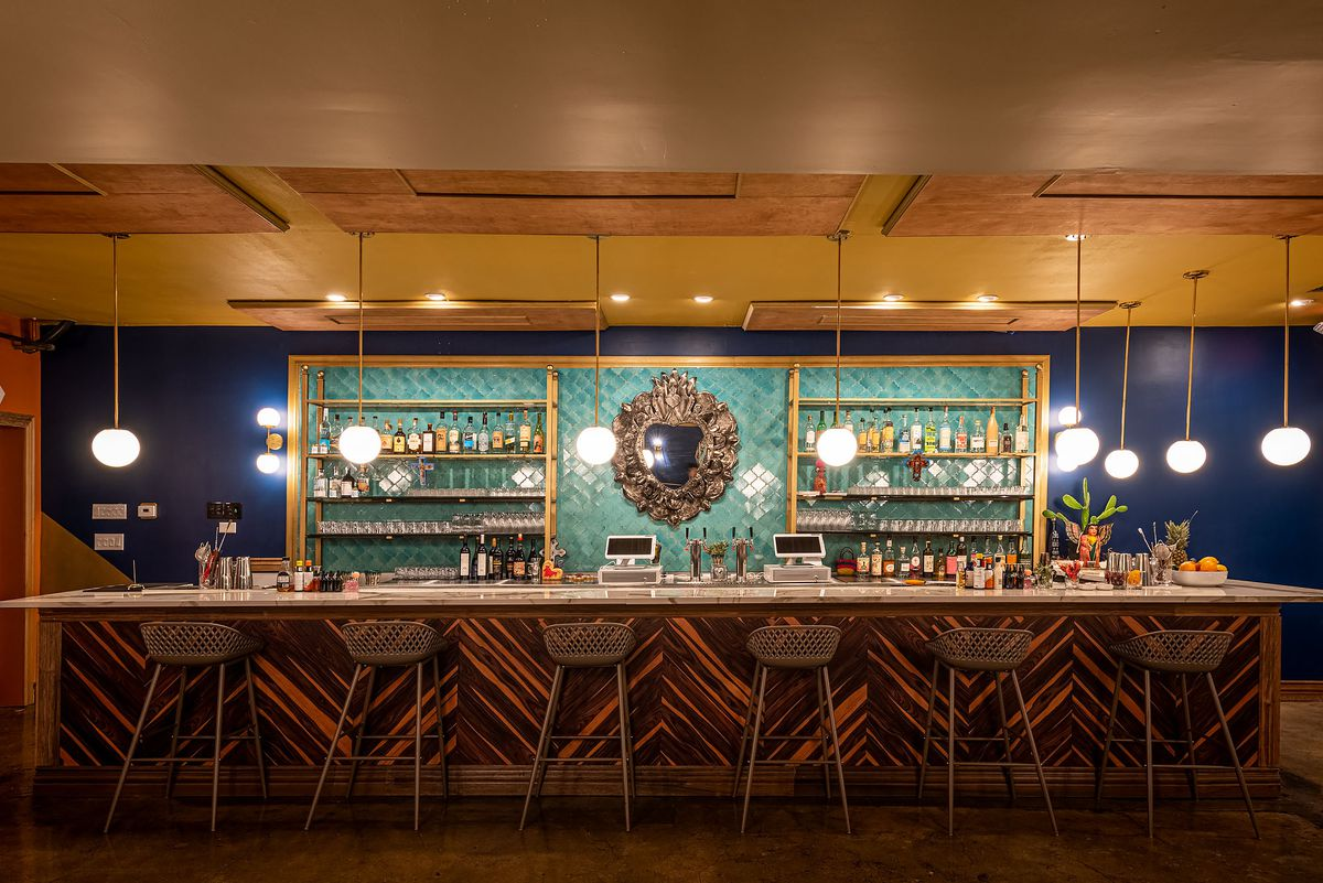A turquoise and gold bar area inside of a new restaurant.