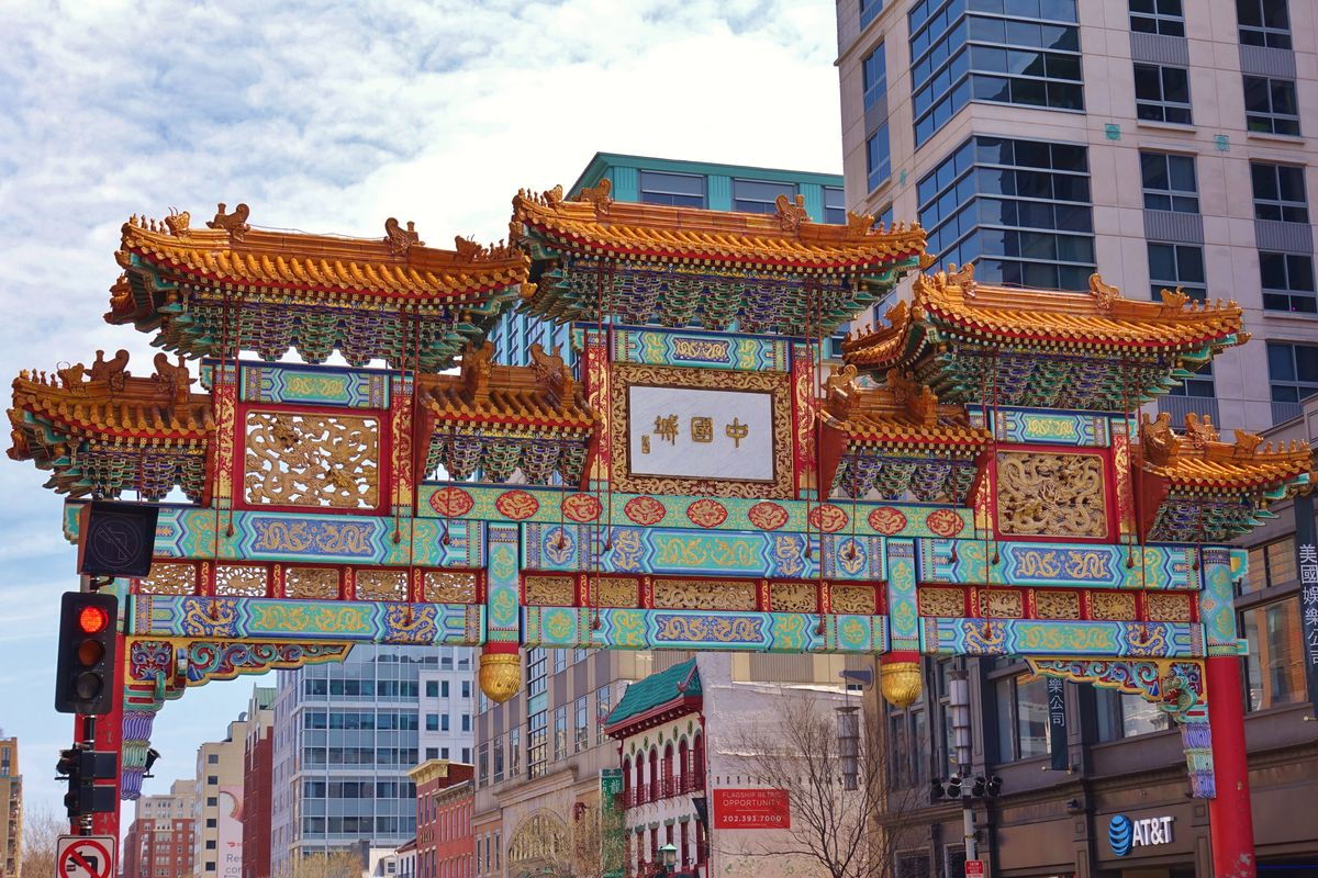 A traditional Chinese archway in an urban area. It has ceramic tiles and many colors.