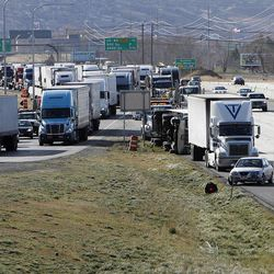 One truck is on its side at center right due to wind as other trucks get off the northbound Centerville exit, Thursday, Dec. 1, 2011.