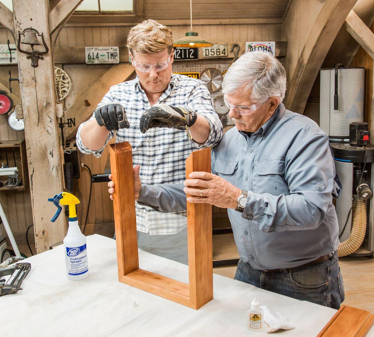Uma pessoa segurando os dois lados da caixa de sombra DIY enquanto a outra desliza o vidro pela parte superior.