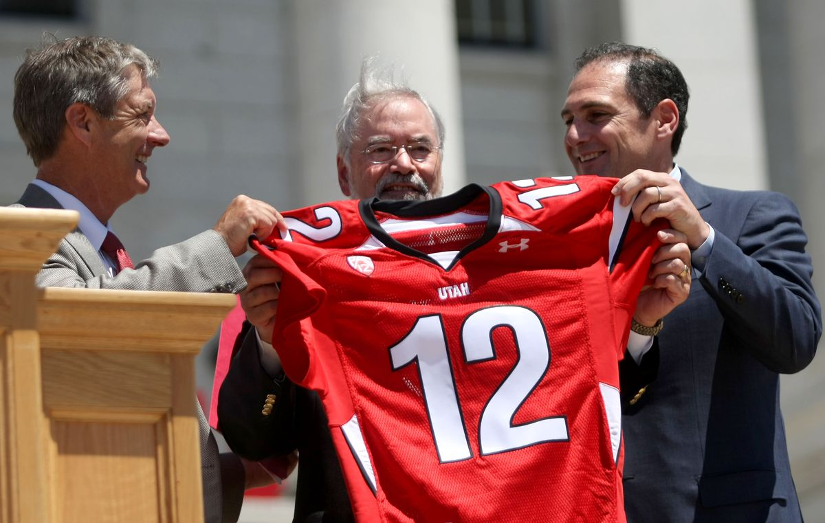 Utah athletics director Chris Hill, left, University of Utah Interim President Lorris Betz, center, and Pac-12 commissioner Larry Scott hold up a Pac-12 Day jersey during Pac-12 Celebration Day at the State Capitol in Salt Lake City on Friday, July 1, 2011.