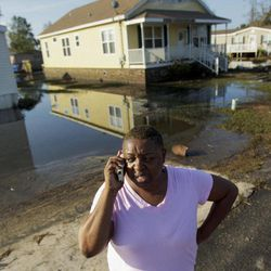 Natachia Riley talks outside the house of her mother, Clara Williams, in Ironton, La., which was flooded from Hurricane Isaac, near Louisiana Hwy 23 in Plaquemines Parish  Monday, Sept. 3, 2012. The house was built seven years ago after mother's previous home was destroyed by Hurricane Katrina.