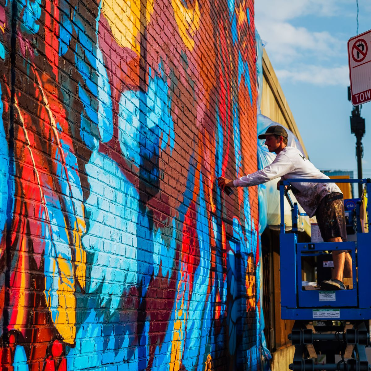 Matt Dean — who works under the name Kiptoe — paints his side of the mural at 488 N. Milwaukee Ave. during the Titan Walls gathering of muralists Aug. 21.
