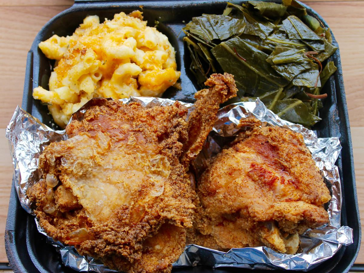 Overhead view of a black plastic takeout container in three sections. The small sections contain mac and cheese and collard greens; the large section contains pieces of fried chicken on aluminum foil. The container sits on a light wooden surface.