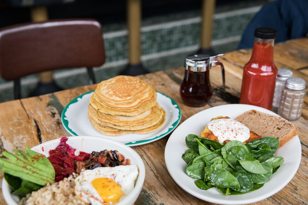 a stack of pancakes, a breakfast bowl, and a salad with quiche