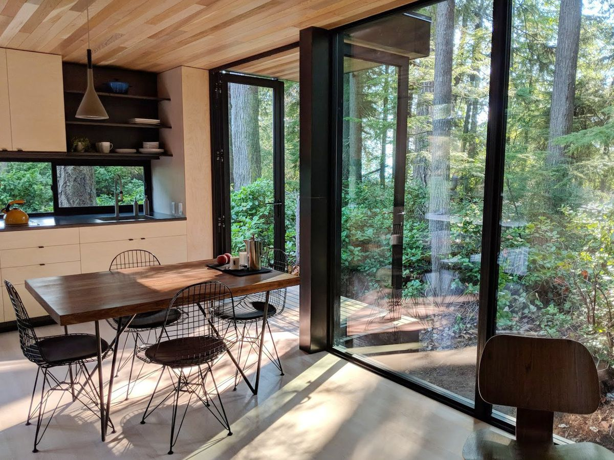 Kitchen with a small table, four wireframe chairs, and large windows that open to the outdoors.