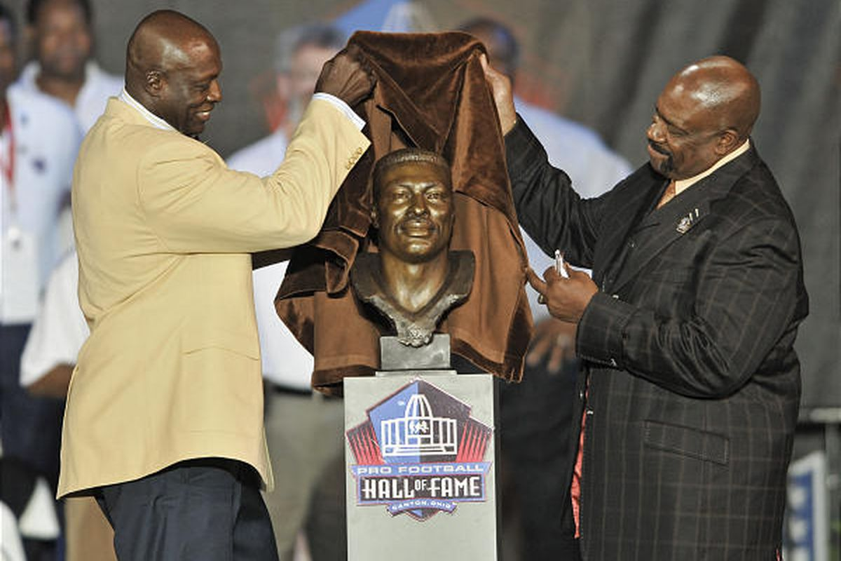Bruce Smith, left, and former Buffalo defensive coordinator Ted Cottrell unveil a bronze bust of Smith during Pro Football Hall of Fame induction ceremony.
