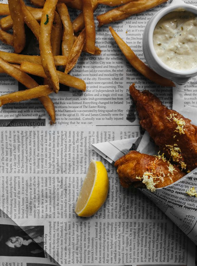 Pieces of fried, battered fish wrapped in newspaper
