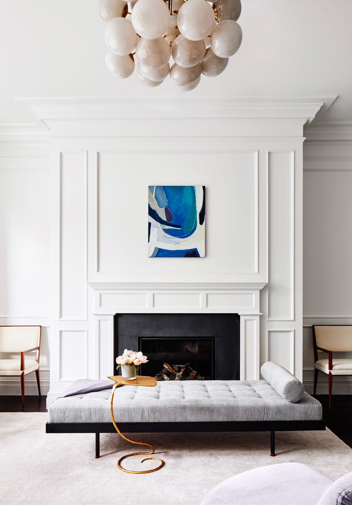 A cluster of globes form a pendant light in the living room. It hangs above a grey tufted daybed that is placed in front of the living room fireplace. Above the fireplace hangs a piece of abstract art with a blue/teal palette.