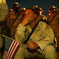 Sgt. First Class William Stephens holds an American flag as he and fellow U.S. soldiers attend an evening vigil at the Al-Salam palace in Baghdad Thursday to remember the victims of the September 11 attacks in the United States.