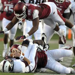 Arkansas defensive end Chris Smith, bottom right, sacks Louisiana Monroe quarterback Kolton Browning for a 16-yard loss as Arkansas defensive end Trey Flowers (86) leaps over the pair during the first quarter of an NCAA college football game in Little Rock, Ark., Saturday, Sept. 8, 2012.