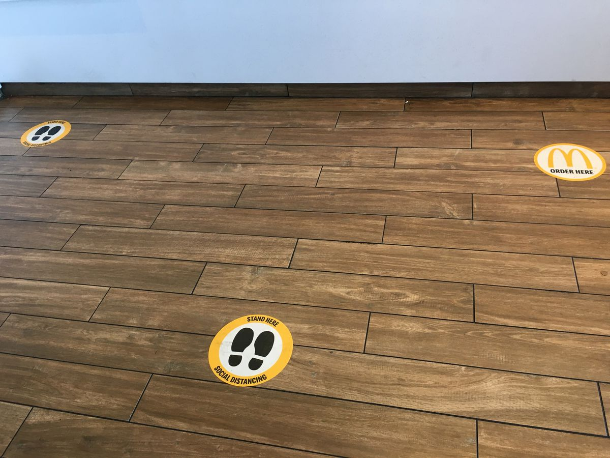 Yellow dots with cartoon shoes on the brown floor indicate where people should stand six feet apart.