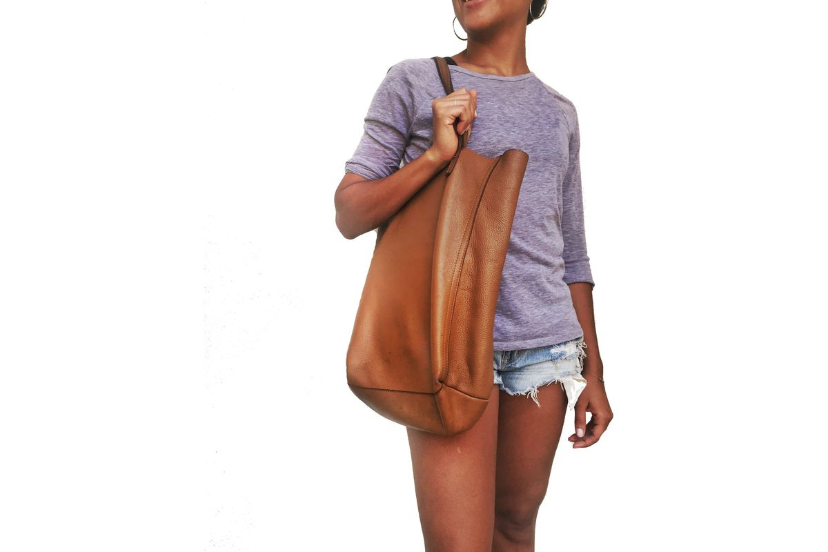 A woman wearing a purple shirt, denim shorts, and carrying a brown leather tote.