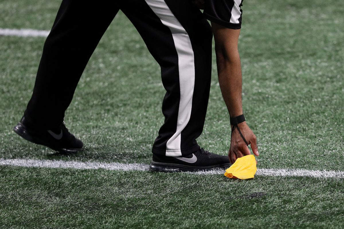A referee picks up a flag in the first quarter during Super Bowl LIII between the Los Angeles Rams and New England Patriots, Feb. 3, 2019.