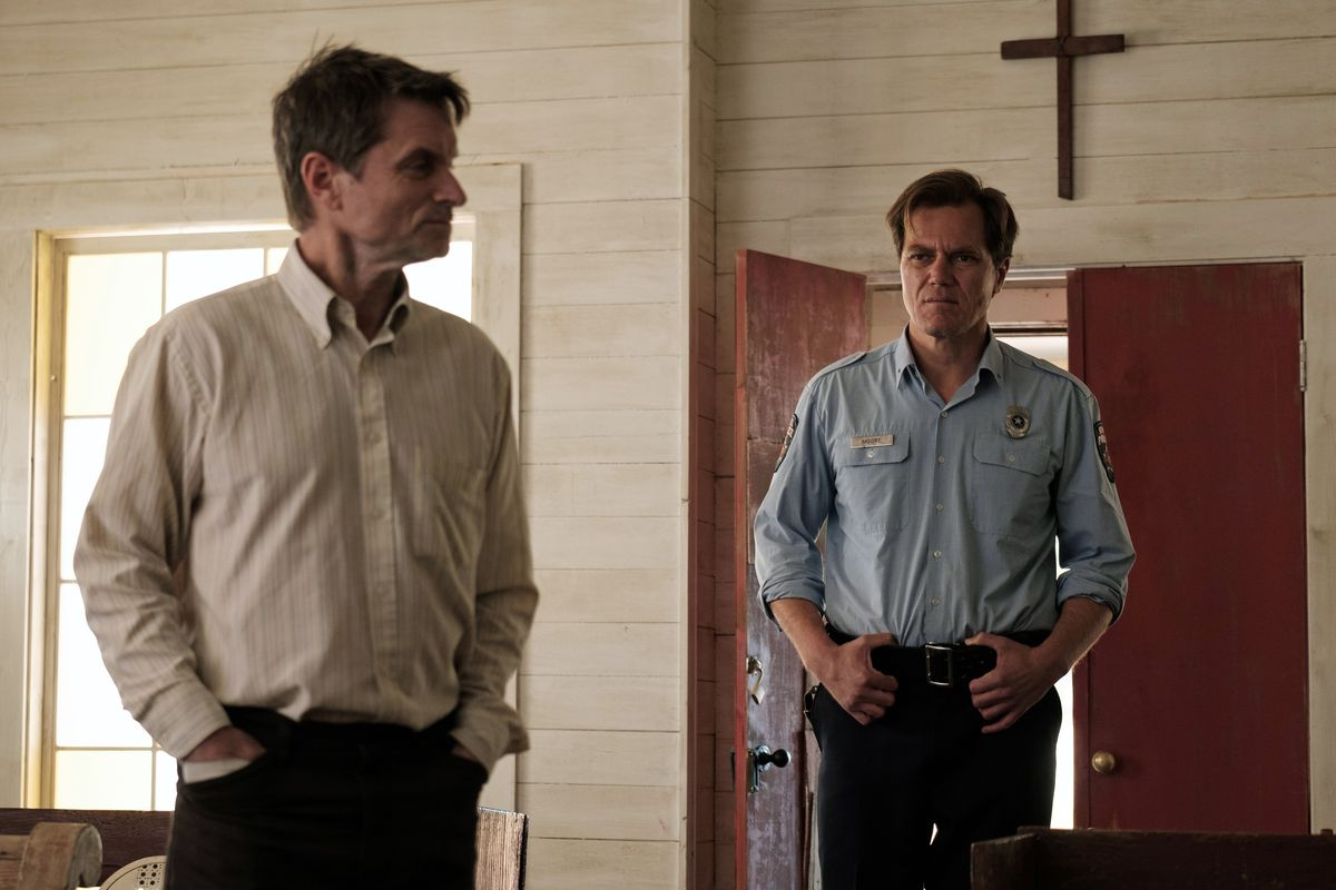 Two men stand in a church with a cross overhead.