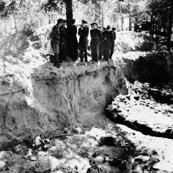 FILE - In this May 1943 file photo, a group of American and British POWs being held by the Germans, including Lt. Col. John H. Van Vliet Jr. and Capt. Donald B. Stewart, look over a mass grave where murdered Polish officers are buried, near Smolensk, Russia. The Soviet secret police killed the Poles in 1940, hoping to eliminate an elite that would have resisted Soviet control of Poland. Van Vliet and Stewart were among a group of British and American prisoners forced to see the horrifying site by the Germans, who wanted word to get out to the world of the Soviet atrocity. Newly declassified documents being opened to the public on Monday, Sept. 10, 2012, by the U.S. National Archives show that Van Vliet and Stewart sent coded messages to Washington after their visit saying they believed the German account of Soviet guilt. It is credible evidence that Washington had relatively early on, but of which it still chose to ignore in order not to jeopardize the alliance with Joseph Stalin.