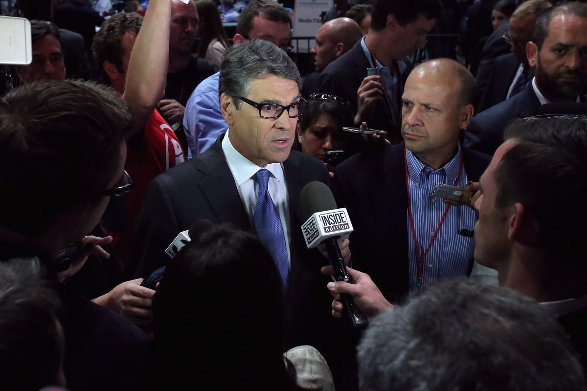 """Republican presidential candidate Rick Perry is surrounded by reporters in """"Spin Alley"""" after a presidential pre-debate forum hosted by FOX News and Facebook at the Quicken Loans Arena August 6, 2015, in Cleveland, Ohio."""