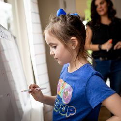 6-year-old Gwendolyn Seger does her homework with her mother, Melissa, and sisters at their home in southern Jordan on Thursday, October 7, 2021.