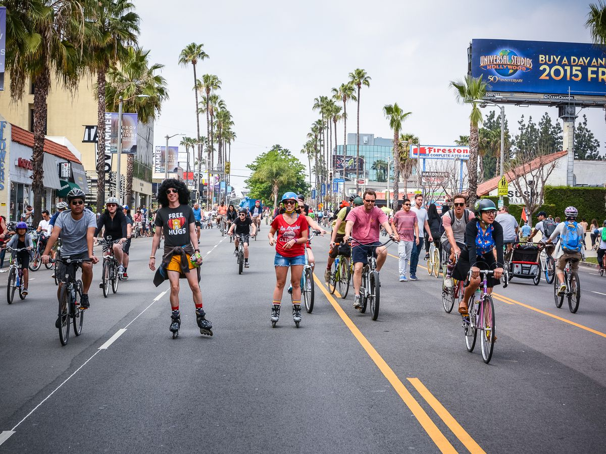 A street with multiple people riding bicycles. The street is lined with palm trees and shops. There is a person with rollerblades on amongst the bicycle riders.