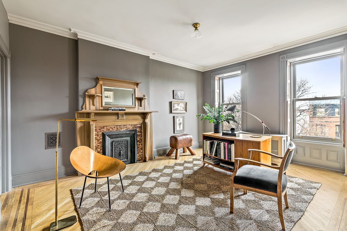 A top-floor bedroom with gray walls and a pale oak mantle is currently being used as an office.