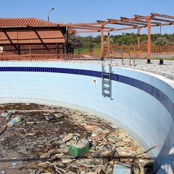 An empty swimming pool collects mud and debris at the Kyllini refugee camp in Myrsini, Greece, July 11, 2016. The camp was previously a luxury resort before it fell into disrepair and was later turned into a refugee camp.