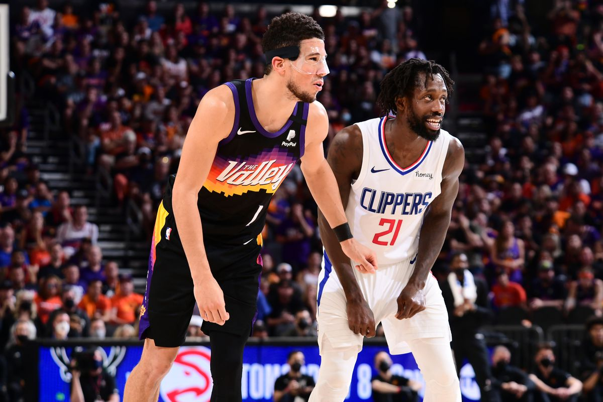 Devin Booker #1 of the Phoenix Suns and Patrick Beverley #21 of the LA Clippers look on during Game 5 of the Western Conference Finals of the 2021 NBA Playoffs on June 28, 2021 at Phoenix Suns Arena in Phoenix, Arizona.