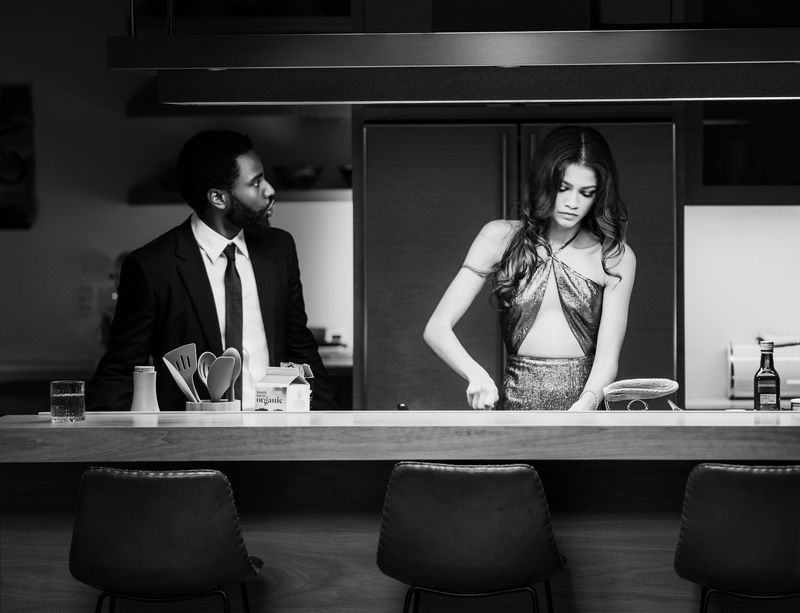 A man and a woman stand at a kitchen counter.