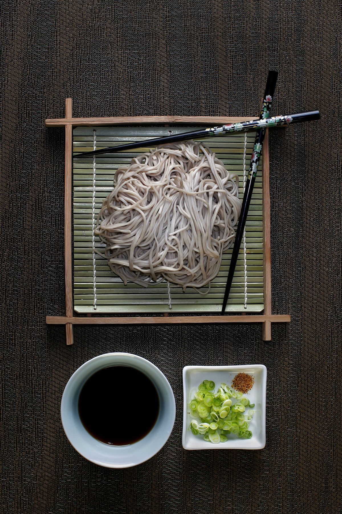 A meal of soba noodles, with tsuyu sauce, chopped green onion and shichimi powder, photographed in
