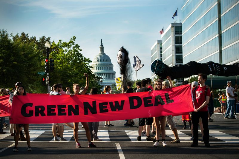 """Climate change protesters block traffic in a Washington, DC, intersection with the US Capitol building in the background. They hold a banner that reads, """"Green New Deal."""""""
