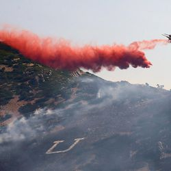 A heavy tanker drops retardant on the mountain as fire burns homes and property near Weber Canyon on Tuesday, Sept. 5, 2017.
