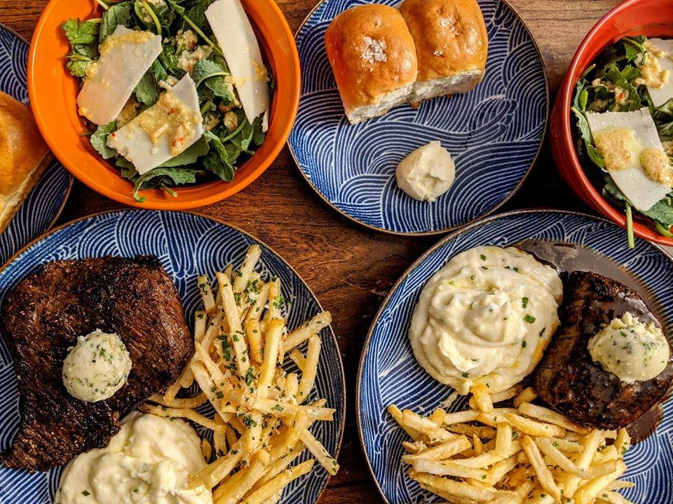 Overhead view of steak, mashed potatoes, fries, rolls, and salad on blue and orange plates on a wooden table