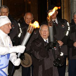 President Gordon B. Hinckley, president of The Church of Jesus Christ of Latter-day Saints, lights an Olympic torch being held by Elder Neal A. Maxwell, a member of the Quorum of the Twelve Apostles, at the Church Administration Building in Salt Lake City on Thursday Feb. 7, 2002.
