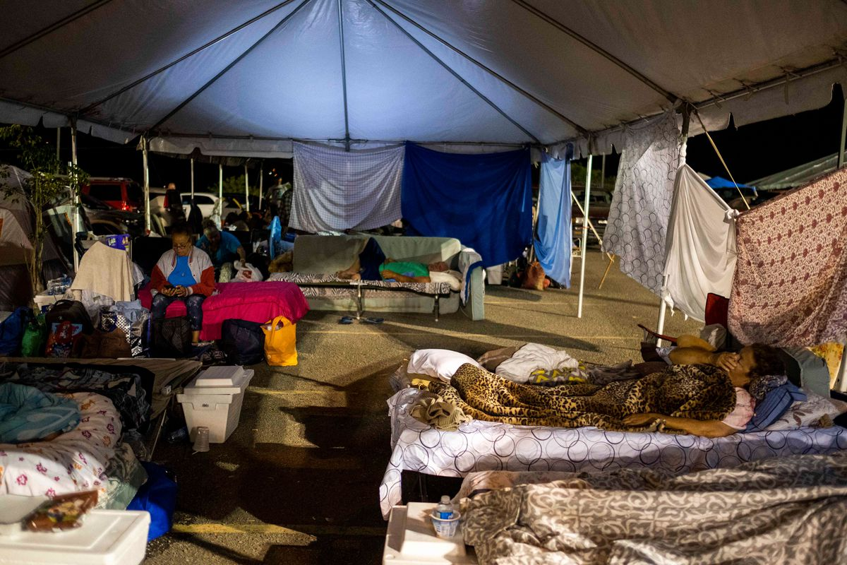Blankets form the walls of a large white tent; people rest on rows of cots.