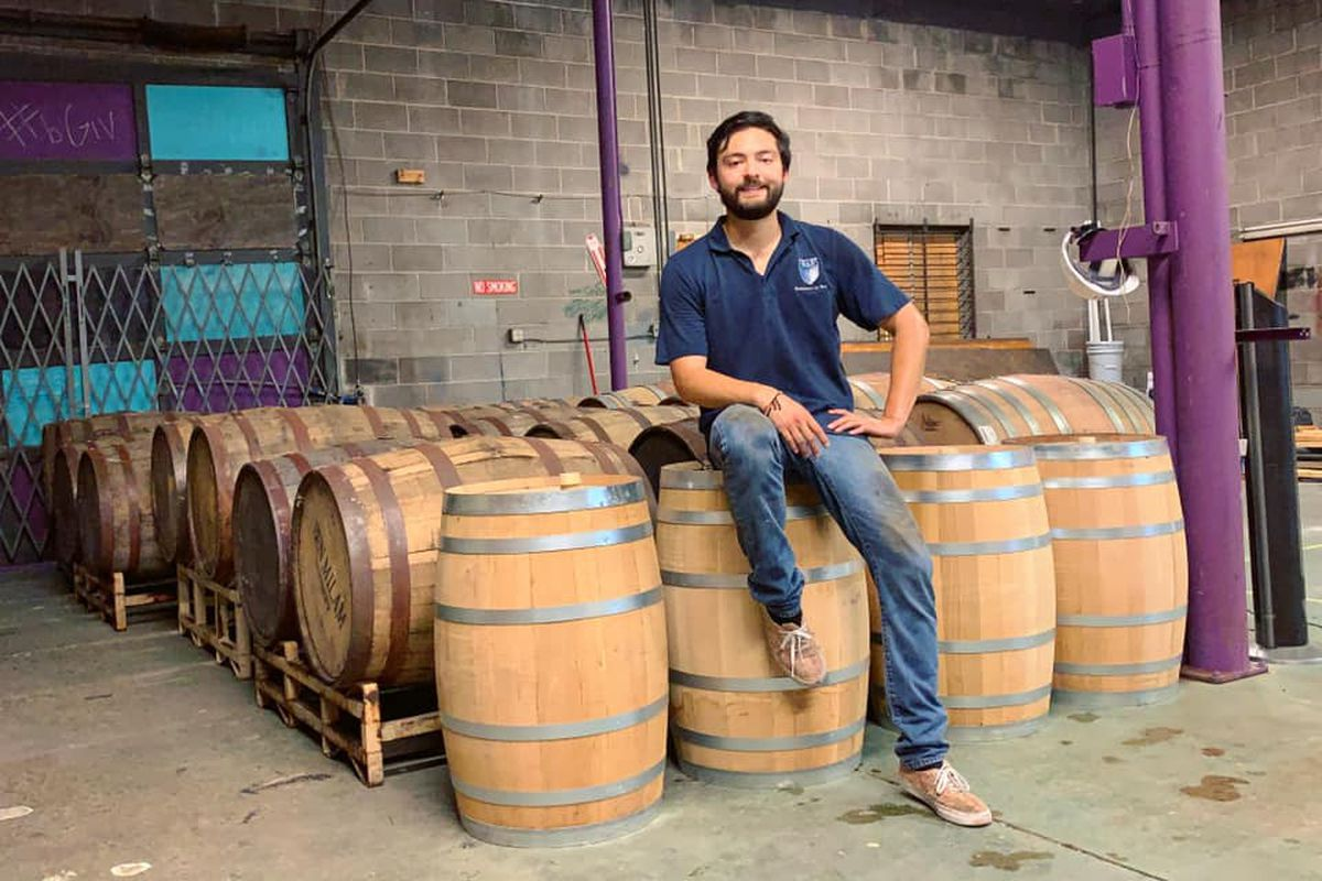 A man sitting on barrels of wine with with concrete bricks behind him that have been painted teal and purple