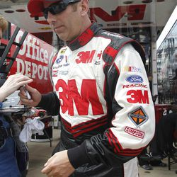 Greg Biffle makes his way from his  trailer to his car before practice for the NACAR Sprint Cup auto race at Texas Motor Speedway on Thursday, April 12, 2012, in Fort Worth, Texas.