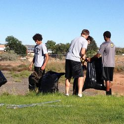 Football players from Union High School clean up weeds as a service project in Roosevelt, Monday, Sept. 23, 2013.