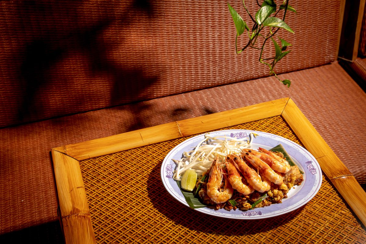 Phat thai with head-on shrimp sits on a white plate on a brown wicker table