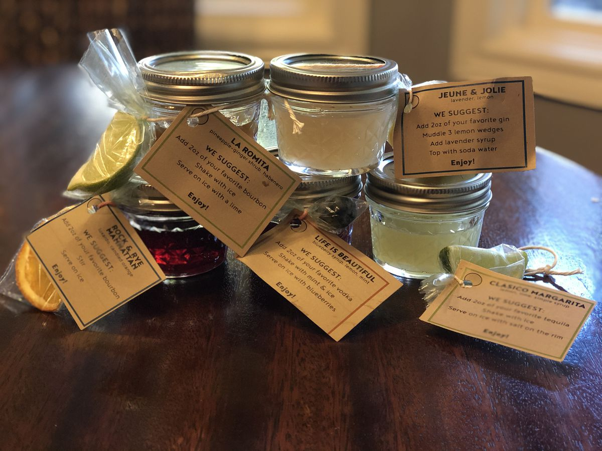Cocktail kits in tiny mason jars with brown paper labels attached.