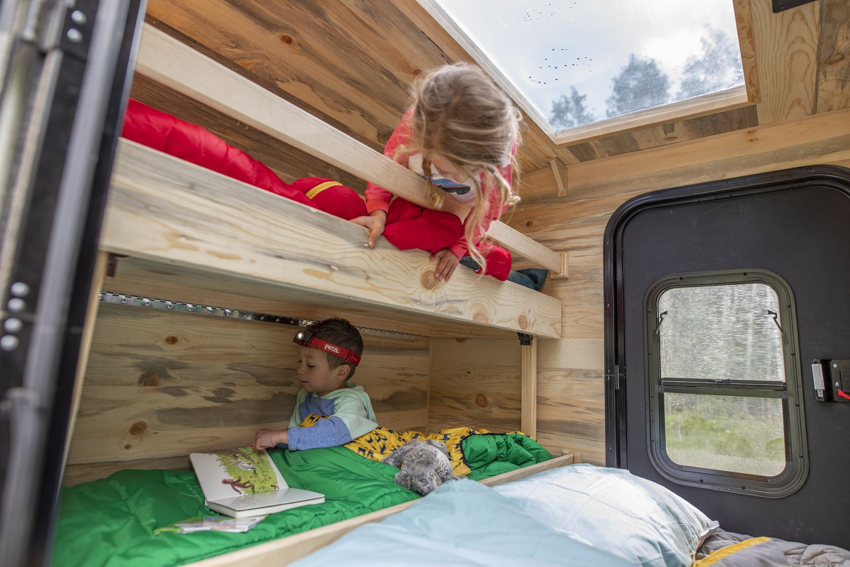 Kids on bunk beds in interior of colorado summit trailer, adffordable campers