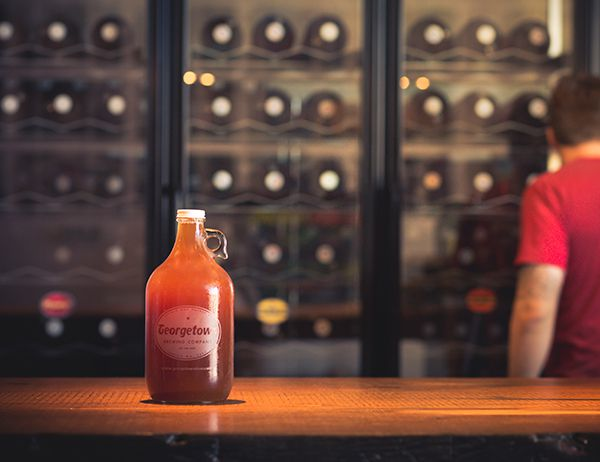 """A growler filled with beer and labeled """"Georgetown"""" sits on a wood counter inside a taproom"""