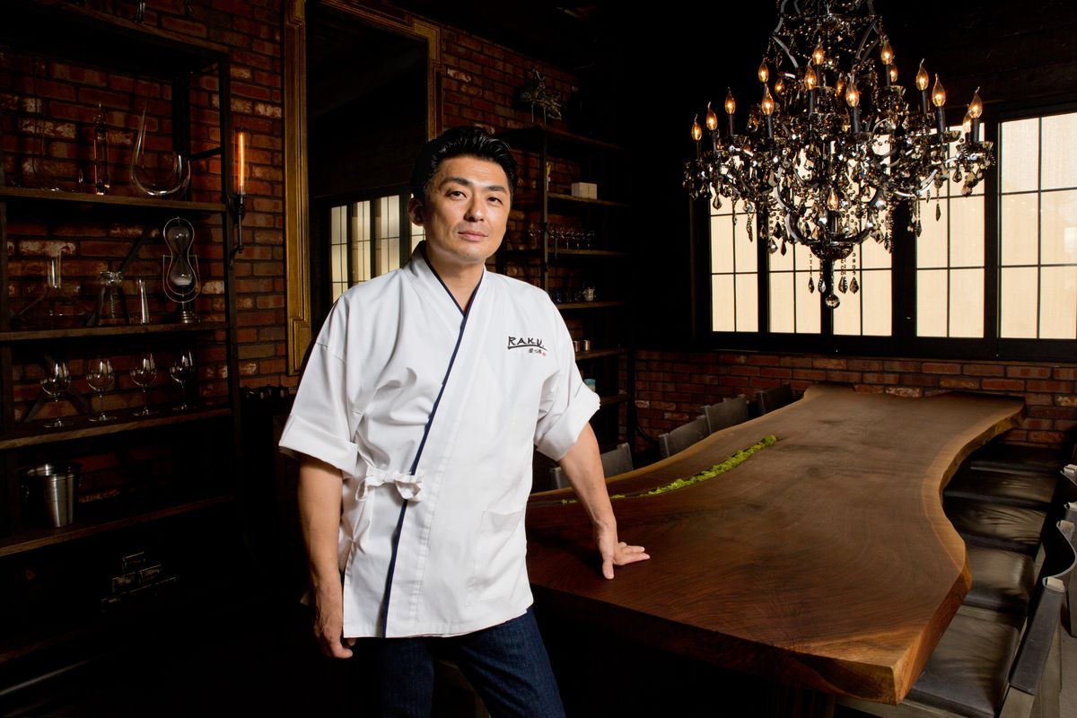 A chef in a white coat leans on a table